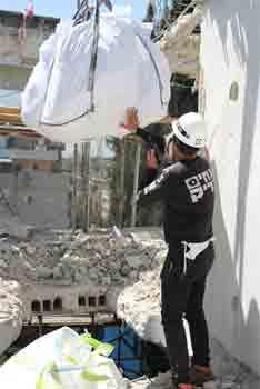 פינוי באלות מלאות פסולת בטון על ידי מנוף בגג בניין על ידי אחים צדיק